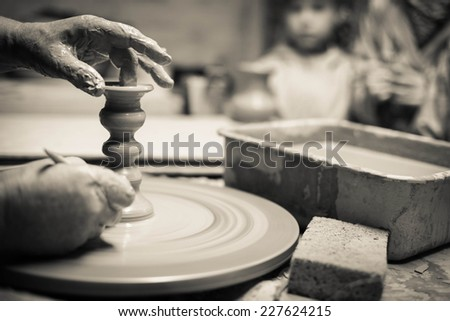 Closeup on potter's hands shaping an edge on the jug - stock photo