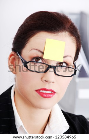 Closeup on pretty caucasian  businesswoman`s face with post it note on her forehead.