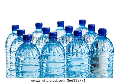 Closeup on rows of refreshing natural mineral water in plastic bottle in white background - stock photo