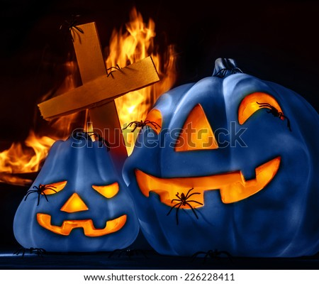 Closeup on scary Halloween decorations, eerie glowing blue carved pumpkin, cross and burning fire on graveyard, uncanny holiday night - stock photo