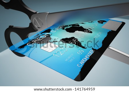 Closeup on scissors cutting creit card on a blue background. Might represent recession, bankruptcy or any financial related matters.