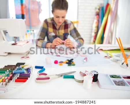 Closeup on seamstress table and seamstress working in background - stock photo