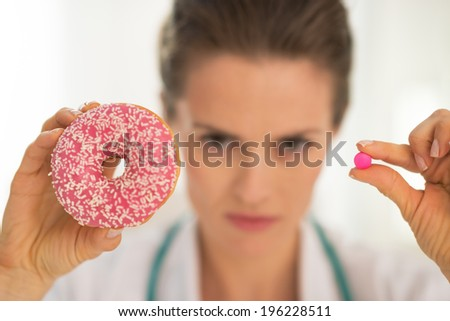 Closeup on serious medical doctor woman showing donut and pill - stock photo