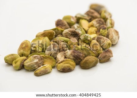 Closeup on shelled pistachio nuts on white background.