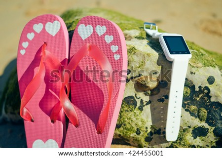 Closeup on smart watch phone and flip-flops on beach background. Top view style, outside fun journey