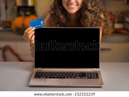 Closeup on smiling young woman with credit card showing laptop blank screen - stock photo