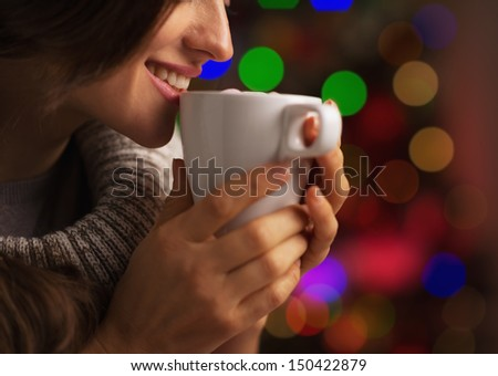 Closeup on smiling young woman with cup of hot chocolate with marshmallow in front of christmas lights - stock photo