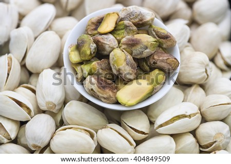 Closeup on some shelled pistachio kernel in small white bowl placed on top of the unshelled nuts.