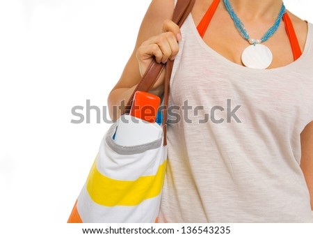 Closeup on sun block creme in bag of beach woman - stock photo