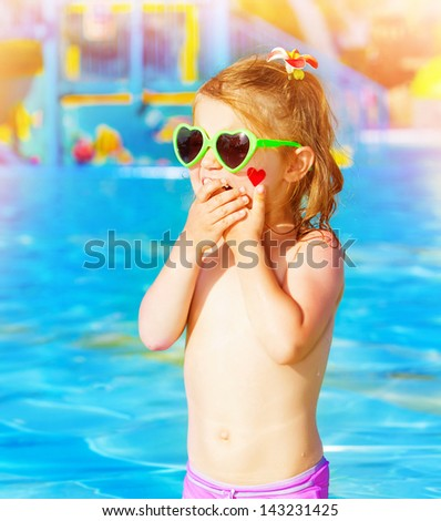 Closeup on sweet baby girl having fun in swimming pool, adorable child with red heart paint print on cheek wearing cute sunglasses, summer holidays in aquapark - stock photo