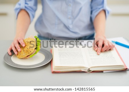 Closeup on teenage girl studying in kitchen - stock photo