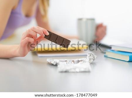 Closeup on teenager girl eating chocolate and studying - stock photo