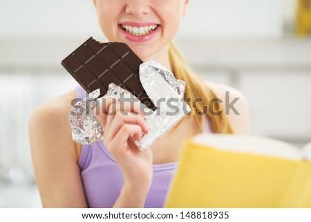 Closeup on teenager girl with book and chocolate bar - stock photo