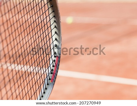 closeup on tennis racket and clay court in the background - stock photo