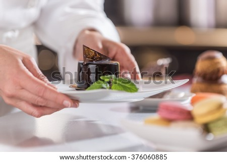 closeup on the hands of a pastry chef in a professional kitchen carefully depositing a gold leaf on a chocolate fondant