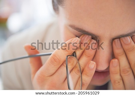 Closeup on tired business woman with eyeglasses - stock photo