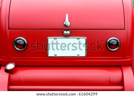 closeup on trunk of a red antique car and license plate - stock photo