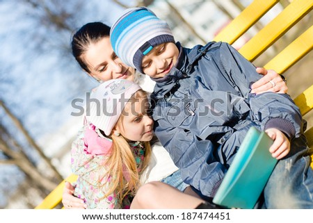 closeup on two kids beautiful children, son and daughter with their mother having fun using tablet pc computer in the park on spring or autumn outdoors background - stock photo