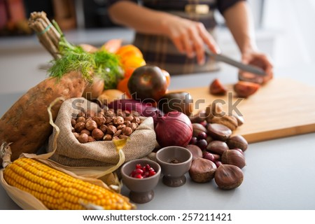 Closeup on vegetables and young housewife cutting cherokee purple tomato - stock photo