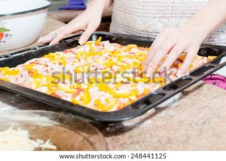 closeup on woman hands preparing a delicious pizza - stock photo