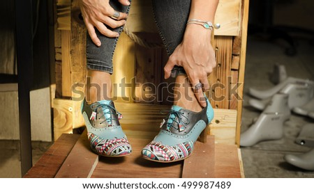 Closeup on woman legs with fashionable hand crafted, custom made high heels, cobbler objects in background (molds for shoes)