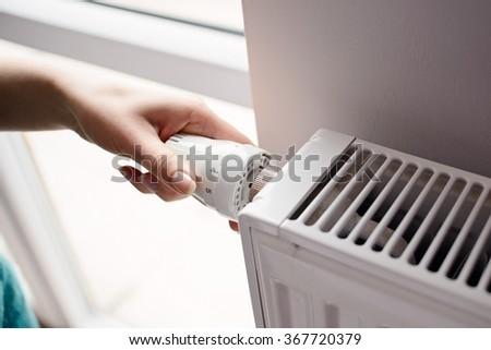 Closeup on woman's hand adjusting thermostat valve - stock photo