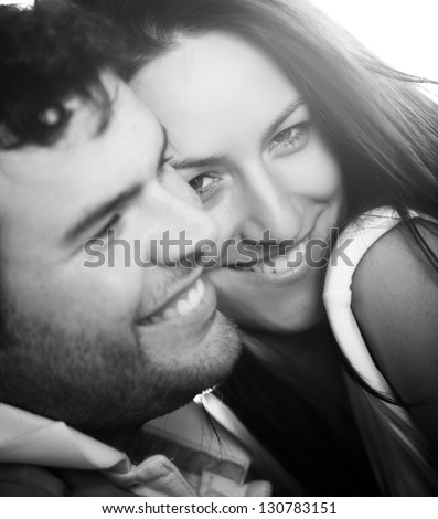 Closeup on young beautiful smiling couple. Focus on him.