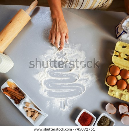 Closeup on young housewife drawing christmas tree on kitchen table with flour