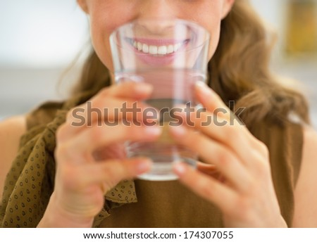 Closeup on young housewife drinking water - stock photo