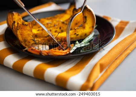 Closeup on young housewife eating baked pumpkin - stock photo
