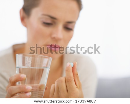 Closeup on young housewife eating pills - stock photo
