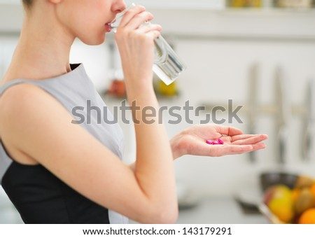 Closeup on young housewife eating pills and drinking water - stock photo