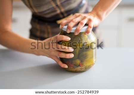 Closeup on young housewife opening jar of pickled cucumbers - stock photo