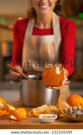 Closeup on young housewife showing homemade orange jam - stock photo
