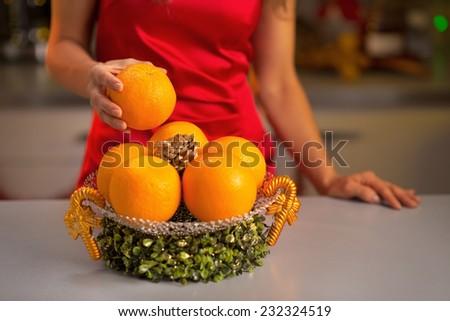 Closeup on young housewife taking orange - stock photo