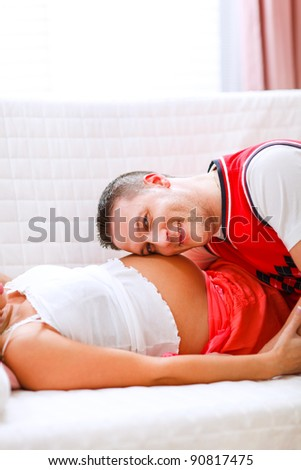 Closeup on young husband listening his pregnant wifes tummy - stock photo