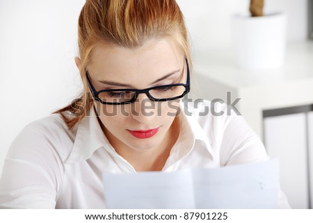 Closeup on young pretty woman in glasses reading files.