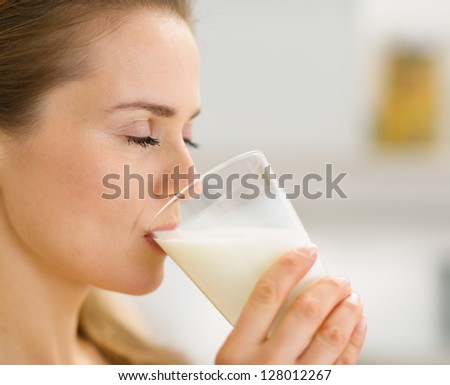 Closeup on young woman drinking milk