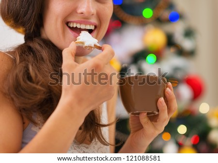 Closeup on young woman eating cookies with hot chocolate near Christmas tree - stock photo