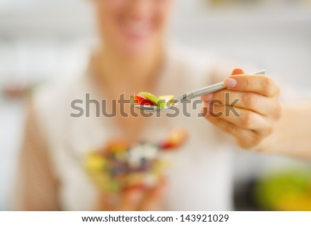 Closeup on young woman giving spoon with fruits salad