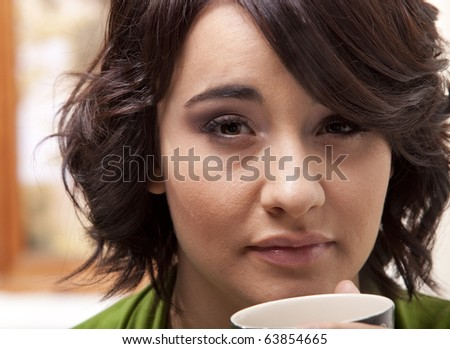 Closeup on young woman with a mug of coffee.