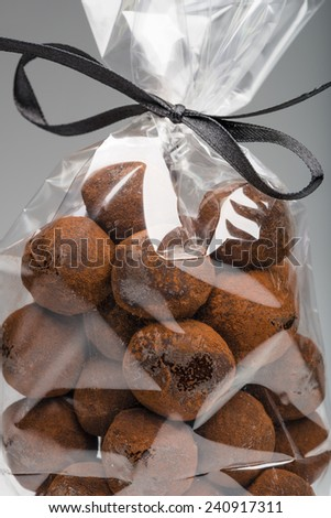 Closeup on yummy chocolate truffles bag with elegant black ribbon for gift. Shooting in studio on grey background. - stock photo