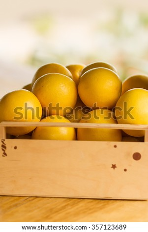 Closeup one timber lug-box full of clean organic natural fresh tasty ripe yellow grapefruits crop fruit full of vitamin for healthy eating diet on light blurred background, vertical picture - stock photo