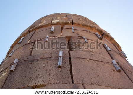closeup one tower of Sillustani(with supporting structures) - pre-Incan burial tombs on the Lake Umayo near Puno, Peru - stock photo