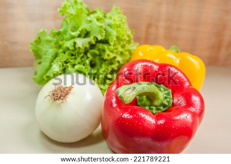 closeup onion ,lettuce.and red yellow paprika for salad on wooden table. - stock photo