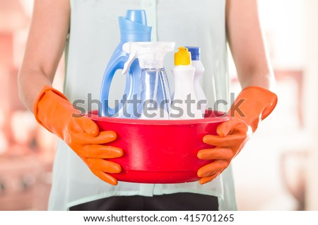 Closeup orange gloves holding red bucket of cleaning products and smiling to camera, housecleaning concept