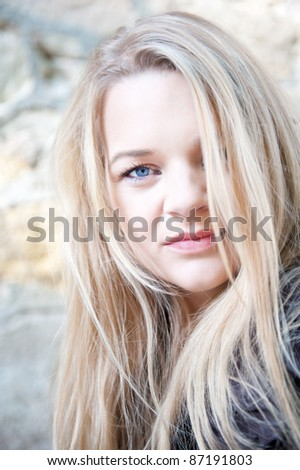 Closeup outdoor portrait of a beautiful young blond woman in front of an old wall