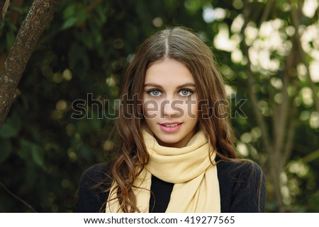 Closeup outdoor portrait of young smiling brunette woman with wavy long hair looking into camera posing against forest park background - stock photo