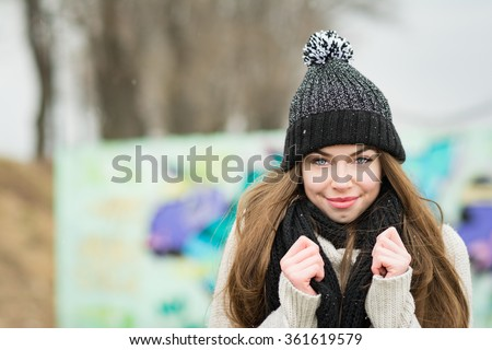 Closeup outdoors portrait of cute teenage girl in black knitted beanie and scarf outdoors on snowy winter day. Cute young woman in cozy knitted hat and shawl. Natural light, mild retouch.