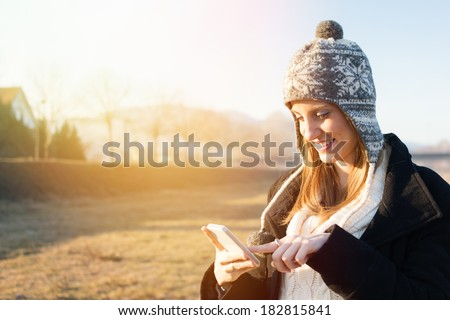 Closeup outdoors portrait of happy young Caucasian redhead student woman using smartphone. Copy space available. - stock photo